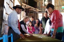 Jovens e adultos aprendem a jogar truco em oficina no acampamento